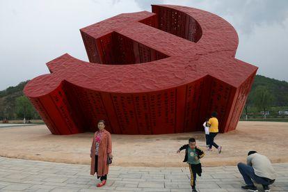 Turistas chineses posam diante de um símbolo do Partido Comunista, em Nanniwan, uma antiga base revolucionária