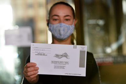 Mulher mostra uma cédula de votação pelo correio nas eleições primárias de Massachusetts, em 1º de setembro de 2020.