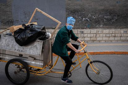 Trabalhador usando uma máscara leva carregamento de lixo em seu triciclo.