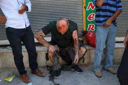 Um ferido espera assistência médica depois do atentado.