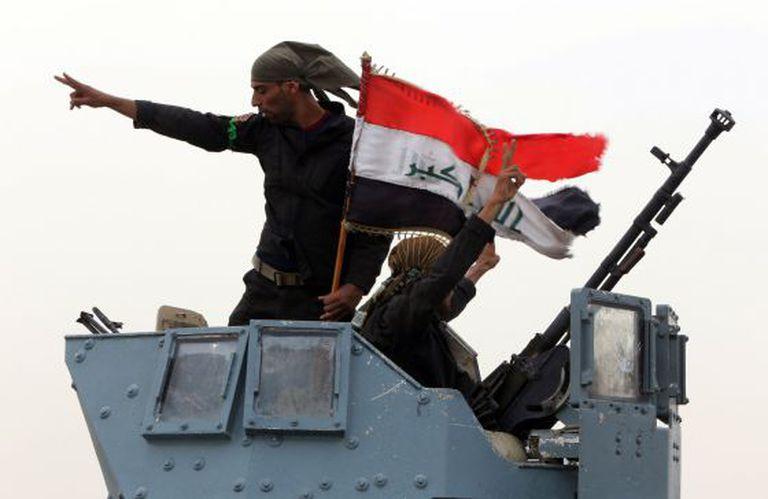 Forças iraquianas celebram a tomada de um posto de controle perto de Mossul.