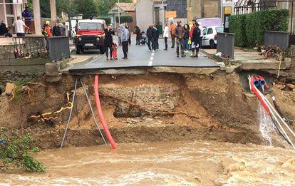Moradores ao lado de uma ponte sobre o rio Trapel arrancada pela força da água em Villegailhenc, perto de Carcassonne.
