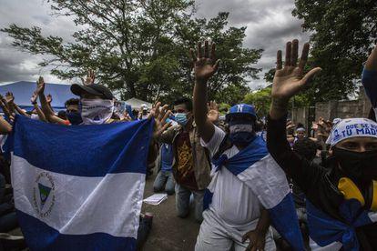 Grupo de amigos e familiares rezam na entrada de El Chipote, o centro para onde são levados os detidos nos protestos.