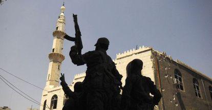 Forças leais a Bashar al Assad levantam suas armas em sinal de vitória em Mleiha, nas proximidades do aeroporto de Damasco.