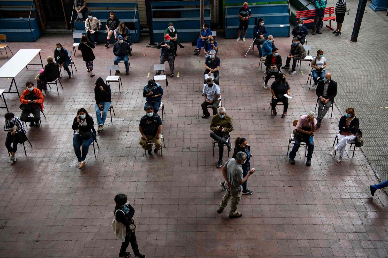 Os professores aguardam sua vez para receber uma dose da vacina chinesa covid-19 Coronavac em um centro de vacinação em Santiago.