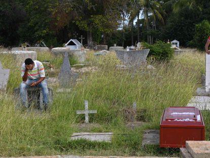 Um homem chora diante de um caixão no cemitério de Güiria, onde foram enterradas as vítimas de um naufrágio no caminho para Trinidad y Tobago.