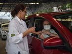 A Public Health worker gives a flu vaccine to a man at a drive-through model in Tijuca neighbourhood in Rio de Janeiro, Brazil, on March 24, 2020. - The Rio de Janeiro state government is requesting people not to go to the beach or any other public areas as a measure to contain the coronavirus pandemic. (Photo by Mauro PIMENTEL / AFP)