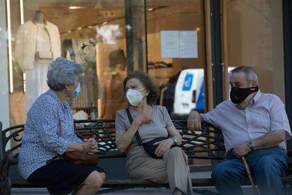 Três pessoas com máscaras conversam sentadas num banco, em Madri, na quarta-feira passada.