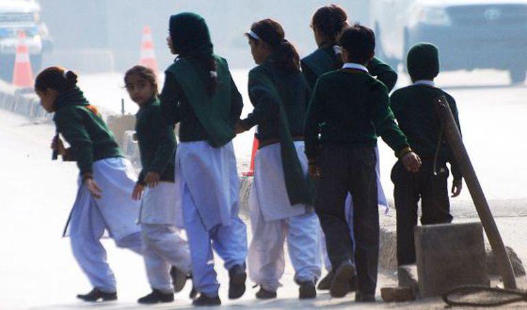 Grupo de estudantes da escola atacada em Peshawar (Paquistão) se afasta do lugar do atentado.