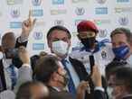 Brazil's President Jair Bolsonaro, center, and Rio de Janeiro's Mayor Marcelo Crivella, right, carry a youth during the inauguration of the new civic-military school General Abreu in Rio de Janeiro, Brazil, Friday, Aug. 14, 2020. They wear masks due to the COVID-19 pandemic. (AP Photo/Silvia Izquierdo)