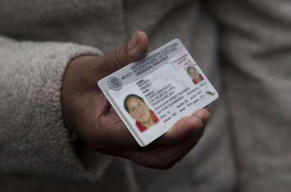 Uma mulher de 30 anos, registrada por Rosa Verduzco, mostra seu documento de identidade obtido hoje.