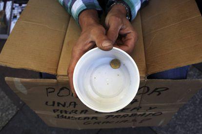 Um mendigo segura um copo de plástico enquanto pede dinheiro em Madri