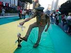 A man kicks a marionette depicting Brazilian President Jair Bolsonaro, during a protest demanding Bolsonaro's impeachment, along Paulista Avenue, in Sao Paulo, Brazil, Saturday, July 24, 2021. Activists called for nationwide demonstrations against Bolsonaro, to demand his impeachment amid allegations of potential corruption in the Health Ministry's purchase of COVID-19 vaccines and his handling of the pandemic. (AP Photo/Nelson Antoine)