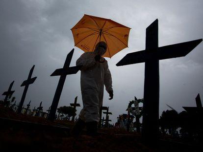 Homem com roupa de proteção passa diante das tumbas com vítimas da covid-19 no cemitério de Nossa Senhora Aparecida, em Manaus (AM), em 25 de fevereiro.