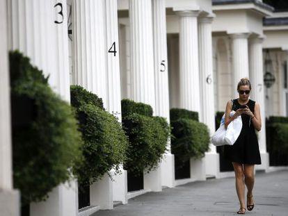 Mulher caminha por uma zona residencial de luxo em Londres.