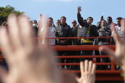 Apoiadores de Jair Bolsonaro levantam as mãos em oração após passeio de moto em São Paulo.
