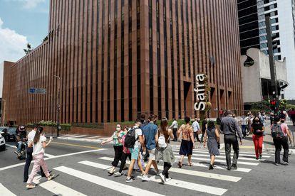 Transeuntes caminham em frente ao Banco Safra na Avenida Paulista, em São Paulo (Brasil).