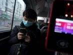 A passenger wearing a face mask checks his mobile phone on a bus, following an outbreak of the novel coronavirus in the country, in Beijing, China February 21, 2020. REUTERS/Stringer  NO RESALES. NO ARCHIVES.