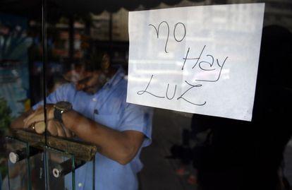 """Empregado atrás da porta de uma loja fechada em Caracas, onde um cartaz avisa: """"Não há luz""""."""