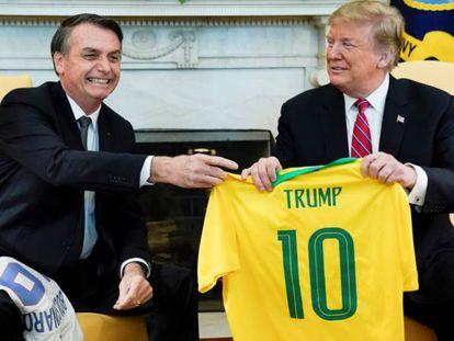 Bolsonaro entrega uma camisa da seleção brasileira a Trump na Casa Branca.