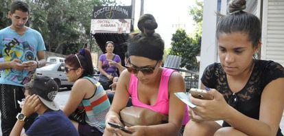 Várias pessoas se conectam à Internet na avenida 23, em Havana.