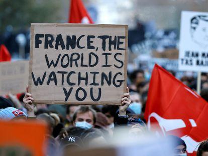 """""""França, o mundo está te observando"""", diz um cartaz na manifestação de sábado em Paris contra a lei de segurança, de Macron."""