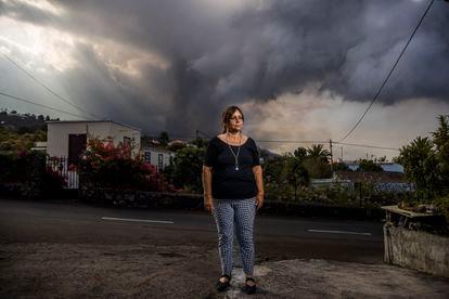Ángeles Nieves, diretora da escola Los Campitos, destruída pela lava em El Paraíso: ao fundo, o vulcão, visto de sua casa, em La Palma.