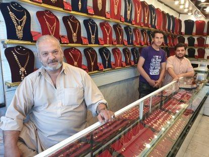 Mohsen Kayumi, com seus filhos, em sua loja de joias de ouro, nesta quinta-feira, em Cabul (Afeganistão).