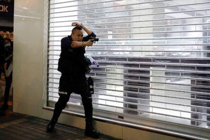 Policial aponta arma para manifestantes em Hong Kong, em fevereiro.