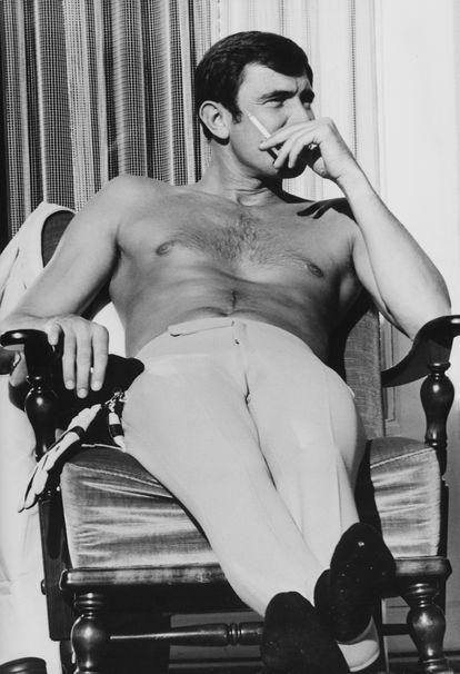 George Lazenby fuma um cigarro durante um descanso nas filmagens de 'A Serviço Secreto de Sua Majestade', em 1969.