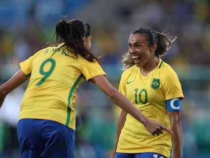 Marta e Andressa comemoram gol na estreia da seleção.
