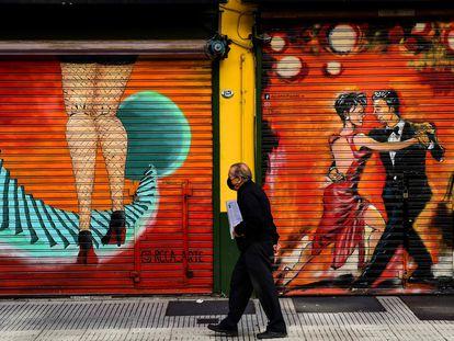 Homem usando uma máscara de proteção caminha em Buenos Aires.