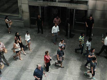 Várias pessoas passam em frente à sede do banco Goldman Sachs, em Nova York.