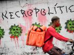 A grafitti is seen on a wall of the Tijuca Health Basic Unit (UPA) showing President's Jair Bolsonaro face inside representations of the COVID-19 virus at the Tijuca neighborhood, Rio de Janeiro state, Brazil, on April 08, 2021. (Photo by Mauro Pimentel / AFP)