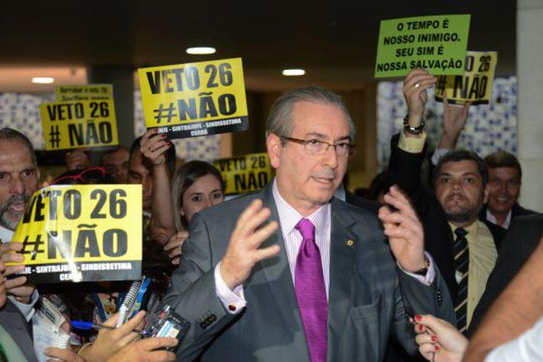 Cunha e cartazes pedindo a derrubada do veto