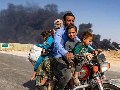 Uma família de deslocados abandona a cidade curda de Ras al Ain na quarta-feira.