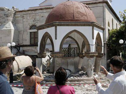 Turistas ao lado de uma construção atingida pelo terremoto em Kos