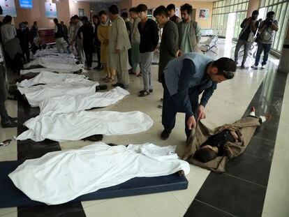 Familiares tentam identificar vítimas de explosões que mataram dezenas de pessoas, entre elas várias alunas de uma escola feminina.