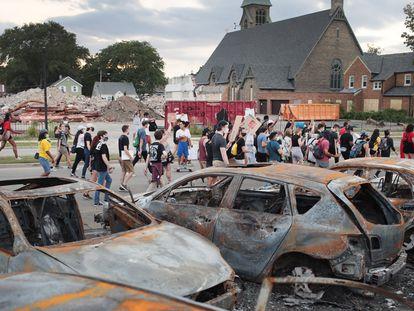 Um grupo de manifestantes pacíficos passa por carros queimados em Kenosha.