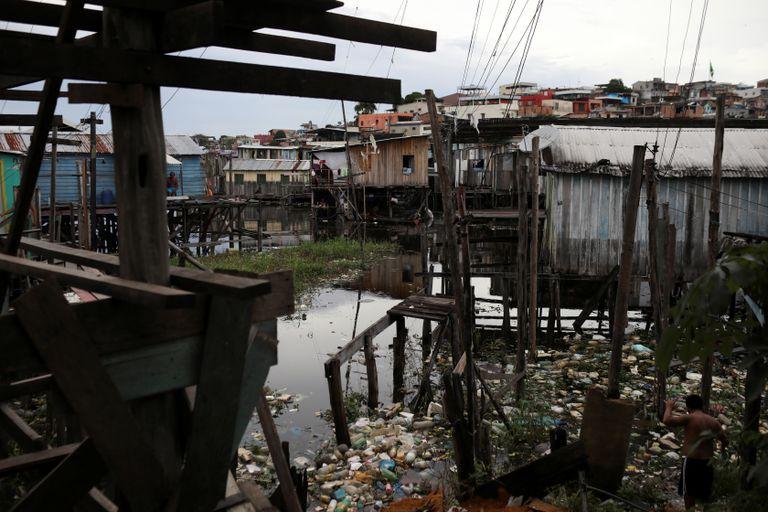 Moradores caminham entre o lixo na região de Educandos, em Manaus, no último 19 de maio.