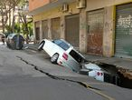 Cars are seen stuck sideways in a huge hole that has opened up next to a Rome apartment building, in Rome, Italy, May 25, 2021. Vigili Del Fuoco/Handout via REUTERS  THIS IMAGE HAS BEEN SUPPLIED BY A THIRD PARTY. DO NOT OBSCURE LOGO