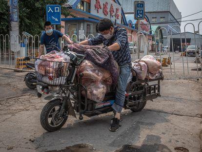 Homens com máscaras protetoras carregam uma moto com carne do lado de fora do mercado Xinfadi, em Pequim.