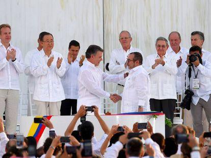 O presidente da Colômbia, Juan Manuel Santos, aperta a mão de Rodrigo Londoño, o Timochenko, líder das FARC, depois da assinatura do acordo final.