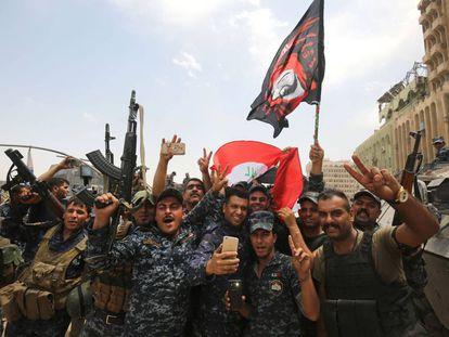 Membros da polícia federal iraquiana dançam com sua bandeira na Cidade Velha de Mossul.