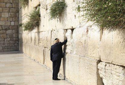 Donald Trump introduz um papel dobrado em uma das fendas dos blocos de pedra, num ritual em que normalmente são expressos desejos ou orações.
