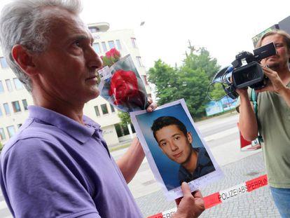 O pai de uma vítima segura o retrato do filho.