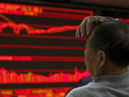 Um homem segue a informação bursátil em Pequim. / REUTERS