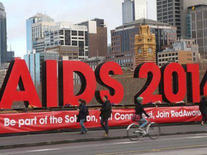 Cartaz em Melbourne, onde se realiza a conferência mundial da Aids. Pessoas deixam flores em homenagem aos 100 especialistas que morreram no voo da Malaysia Airlines, que caiu na Ucrânia.