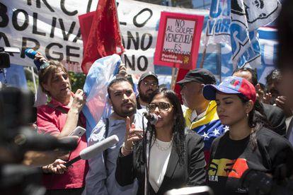 A chanceler da Venezuela, Delcy Rodríguez, fala em Buenos Aires na frente do Ministério das Relações Exteriores rodeada por manifestantes.
