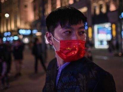 Um homem se protege com uma máscara com as cores da bandeira chinesa numa rua de Xangai.